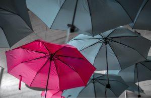 Bright umbrella amongst grey ones